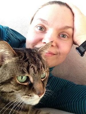 Amanda behind a cat with green eyes